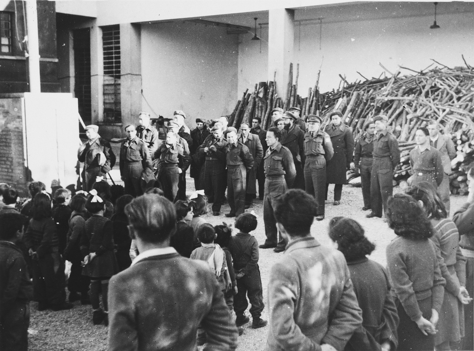 Children and youth stand at attention during a gathering with a delegation from the Joint Distribution Committee in the Selvino children's home.  A chache of weapons can be seen in the rear.  Moshe Zeiri, the director of the Selvino home, is standing in middle with his hands behind his back.