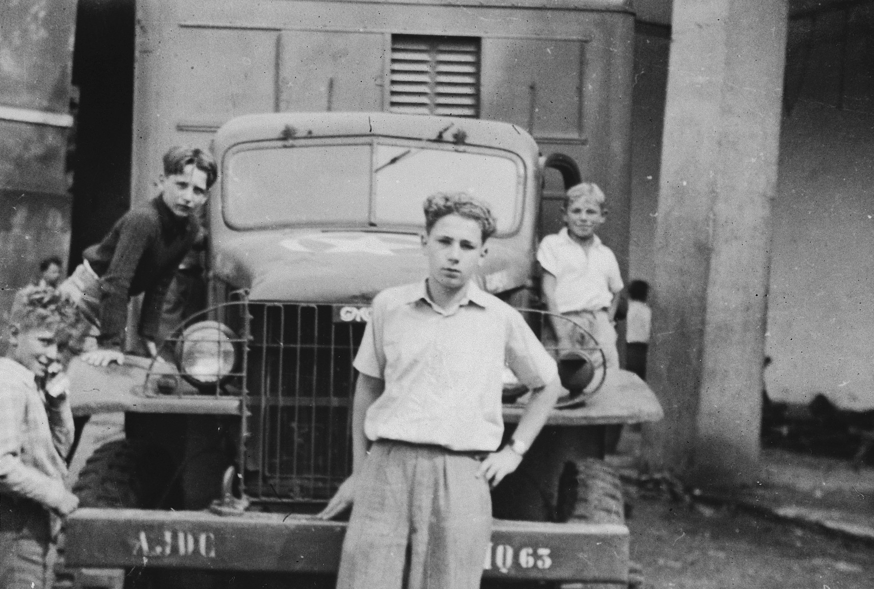 Children crowd around an AJDC truck outside the Selvino children's home in Italy.  Simon Frumkin is pictured in the foreground.