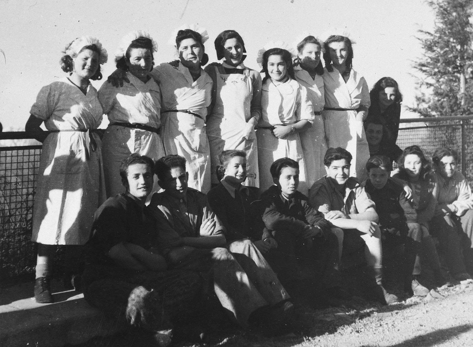 Group portrait of the kitchen staff and teenagers at the Selvino children's home.  The girls were issued special uniforms in honor of a visit by the AJDC.  Among those pictured (bottom row, middle) is Esther Goldman who was working in the kitchen.
