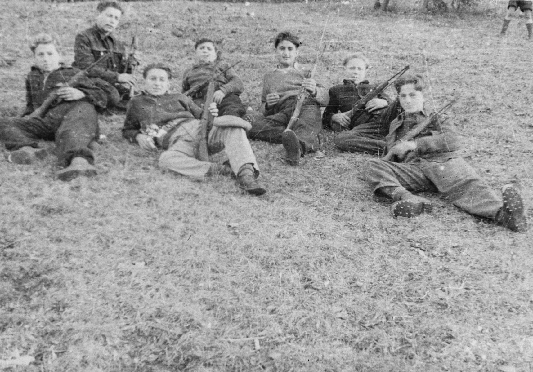 Teenage boys lie in the grass holding weapons during paramilitary training in the Selvino children's home.  The boys were issued real weapons, Italian 22 caliber guns with attached bayonets, but no ammunition.