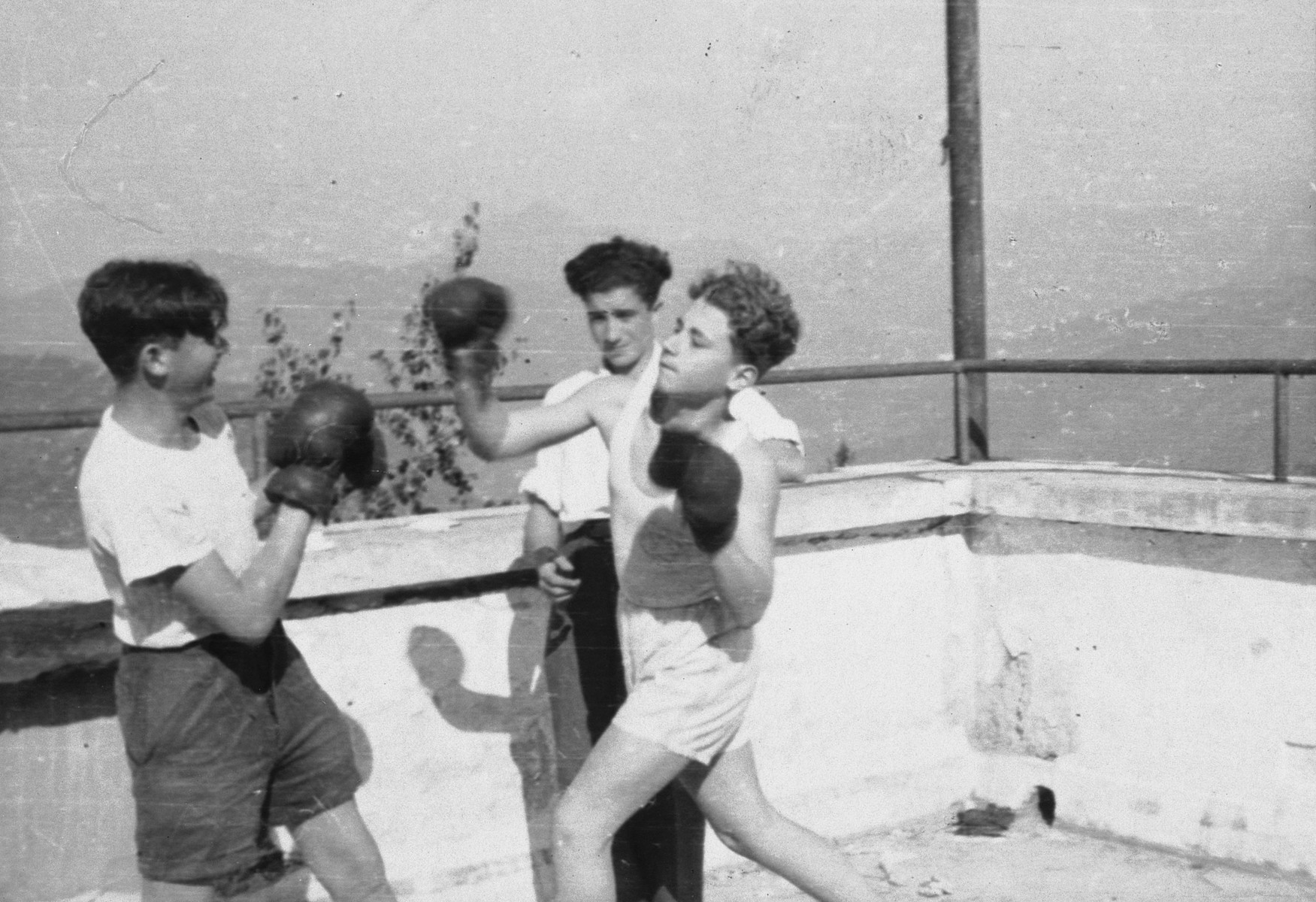 Two teenage boys spar on a balcony of the Selvino children's home in Italy.  Simon Frumkin is on the right.  A Hungarian survivor is on the left.  The JDC supplied the boxing gloves.