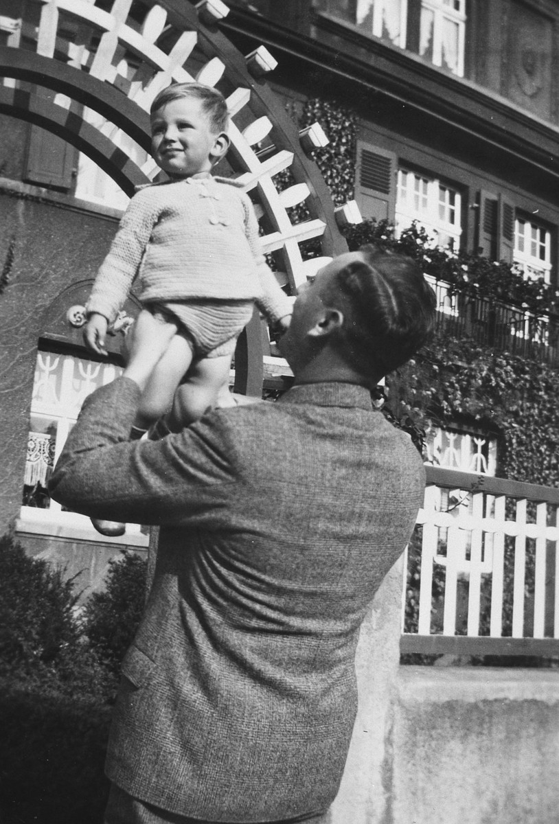 A German-Jewish father lifts his young son high in the air.  Pictured are Karl and Rolf Blumenthal in front of Rolf's paternal grandfather Julius Blumenthal's house at 5 Ostring in Hamm.
