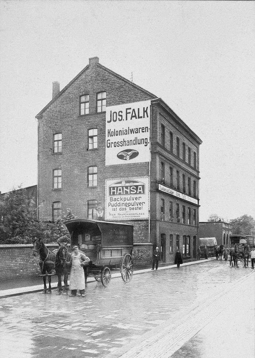 A man stands with his cart and horses outside a business.  Pictured is the company building of Rolf Blumenthal's paternal grandfather, Julius Blumenthal (who partnered with Josef Falk.)