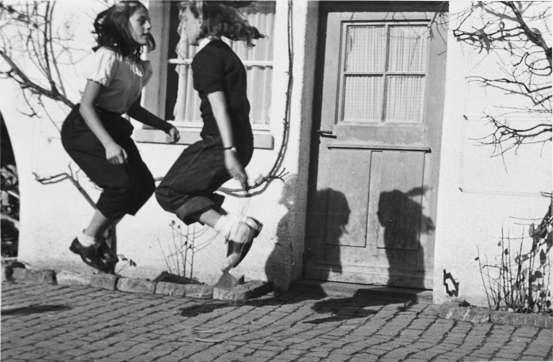 Two girls skip rope outside an international boarding school in Switzerland.  The two girls are from Switzerland and the United States.