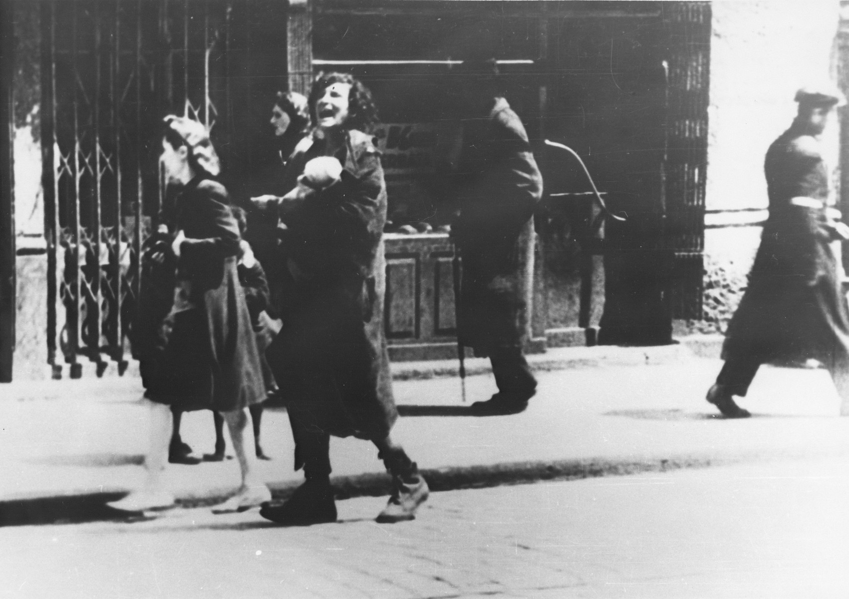 A destitute woman carrying a dead infant cries out as she walks along a street in the Warsaw ghetto.