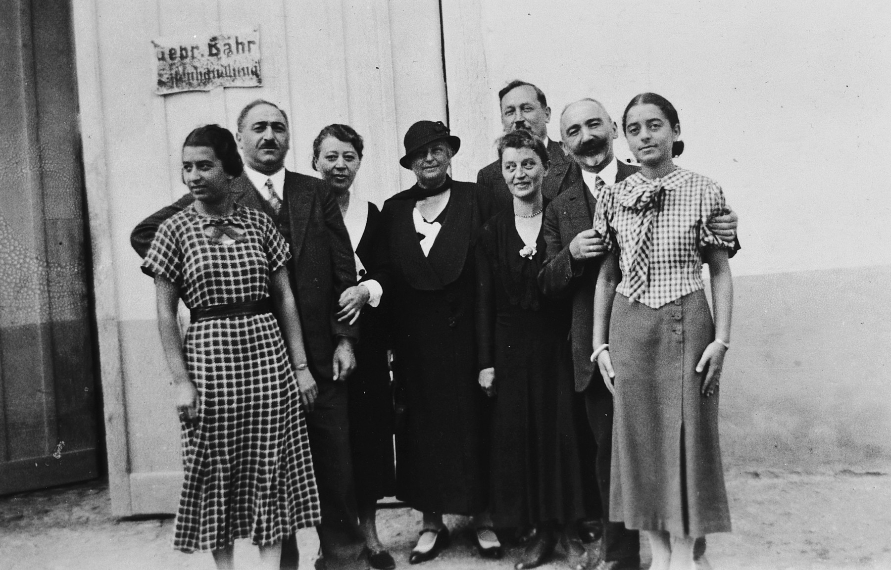 Group portrait of a large German-Jewish family in Breisach.  Pictured from left to right are Ruth Bähr, Julius Bähr, Natalie Bähr, and unknown couple, Fanny Bähr, Hermann Bähr and Margot Bähr.  The sign on he door reads Gebrueder Bähr  Eisenhandlung (Bähr Brothers Plumbing Supply).