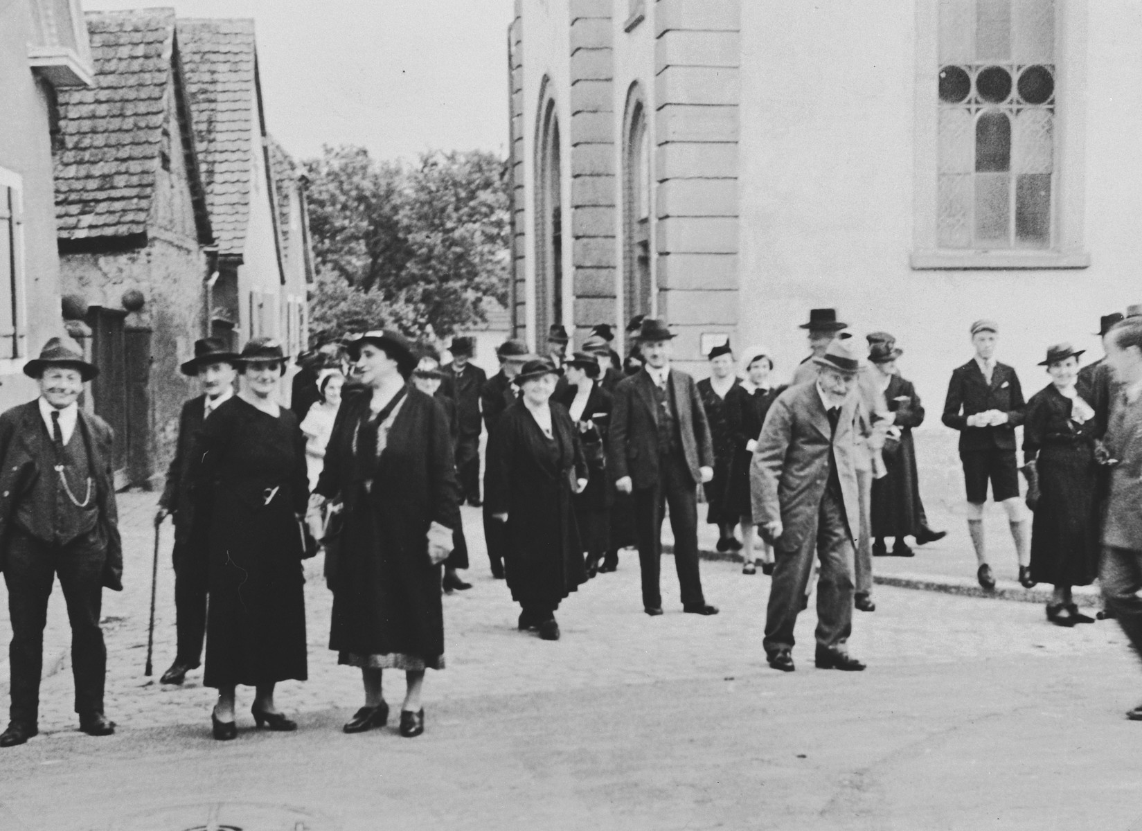 German Jews leave the synagogue on Judengasse at the end of Sabbath morning services.  This is part of series of photographs taken of the Breisach Jewish community 1937.  In October 1940 the entire community was deported to the Gurs internment camp in southern France.
