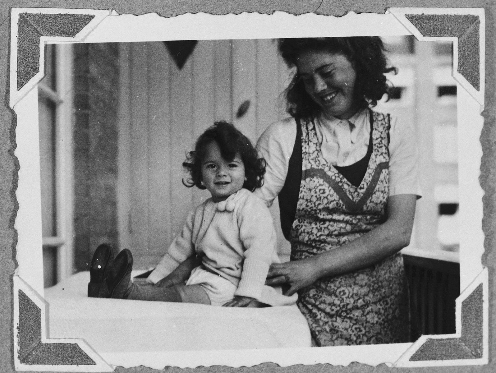 A young Jewish child sits on the balcony table next to her nurse maid.  Pictured is two-year-old Suzanne Hochherr.