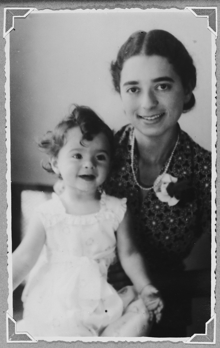 Studio portrait of a German-Jewish refugee in the Netherlands holding her baby girl on her lap.  Pictured are Margot and Suzanne Hochherr.