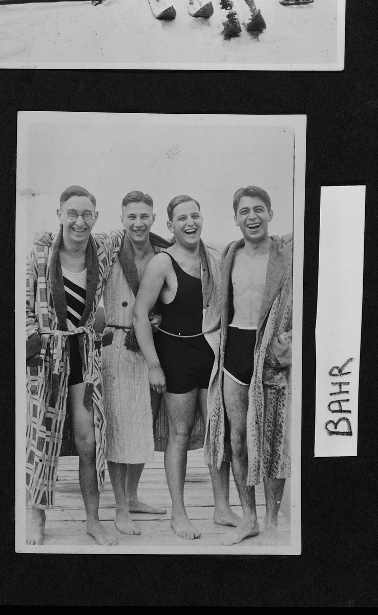 Four German-Jewish university friends wearing swimsuits pose together on a boardwalk.  Heinz Bähr is on the far right.