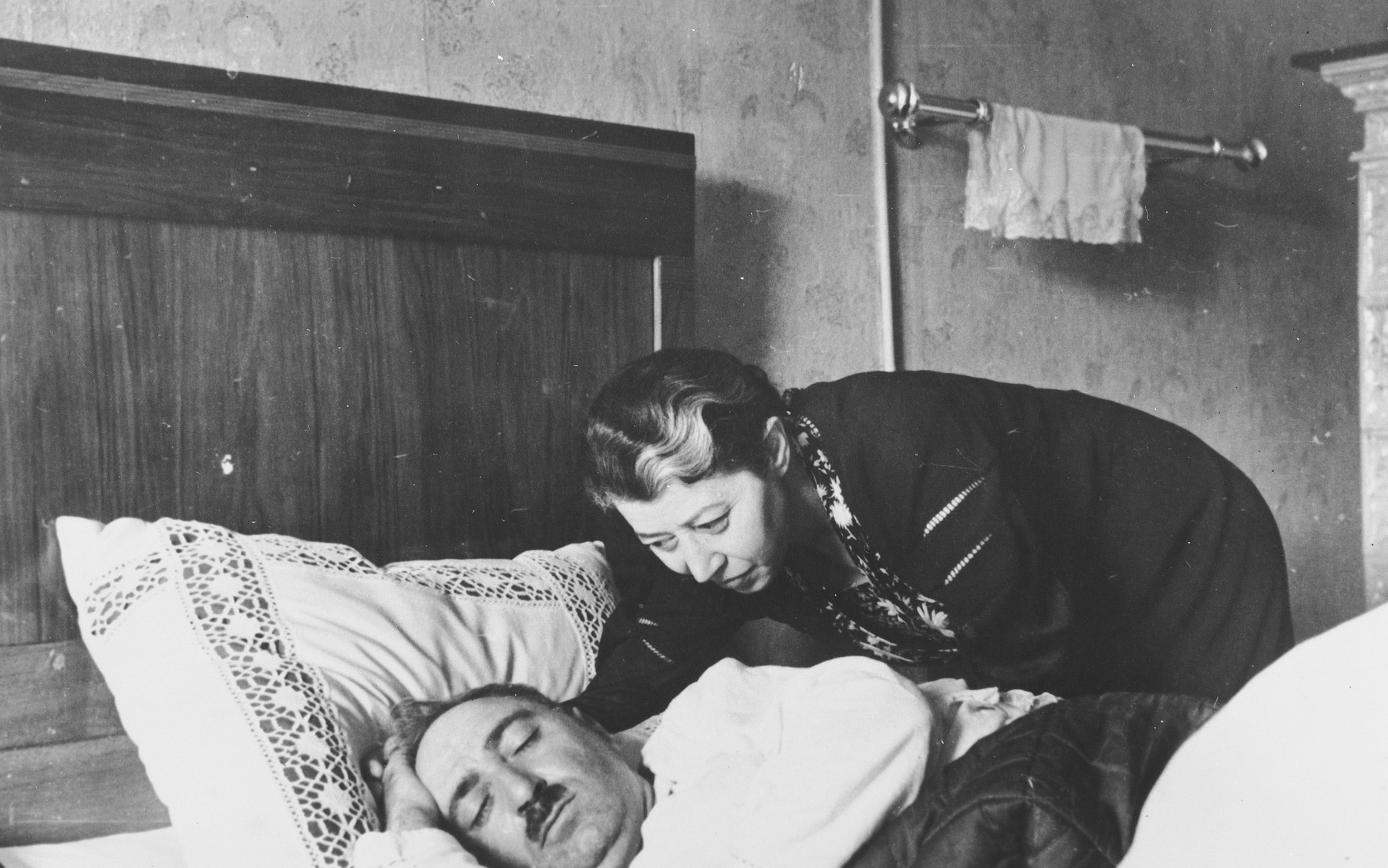 A German-Jewish wife leans over her sleeping husband.  Pictured are Julius and Talie Bähr.  This is part of series of photographs taken of the Breisach Jewish community 1937.  In October 1940 the entire community was deported to the Gurs internment camp in southern France.