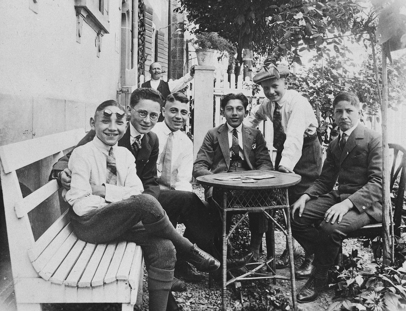 A group of adolescent Jewish friends gather around a small outdoor table in a backyard garden in Breisach.  Pictured from left to right are Hans Frank, Hans Wurmser, Heinz Bähr, unknown and  Luli Weil.  Emil Weil is in the back.  Emil Weil, who had owned a liquor store, perished in Auschwitz in August 1942.