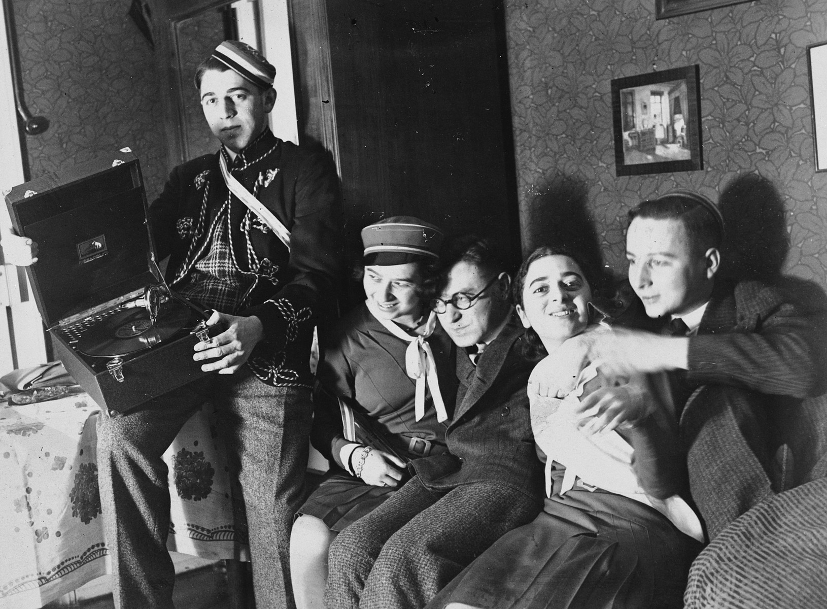 Five German-Jewish university students squeeze together on a couch.  One is holding a phonograph.  From left to right are Heinz Bähr, Ruth Bähr and Margot Bähr is second from the right.  Heinz is wearing the cap and jacket of the KC Jewish fraternity.