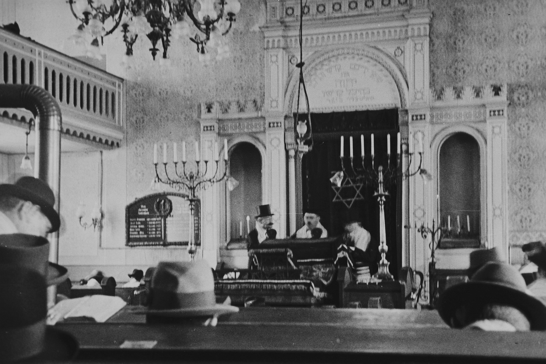 German Jews gather for Sabbath morning prayers in the synagogue in Breisach.  Cantor Michael Eisemann is leading the services.  To his left is Siegfried Weil.  (Though it is normally forbidden to photograph Sabbath services, an exception was made for the purpose of documenting the community.)  This is part of series of photographs taken of the Breisach Jewish community 1937.  In October 1940 the entire community was deported to the Gurs internment camp in southern France.