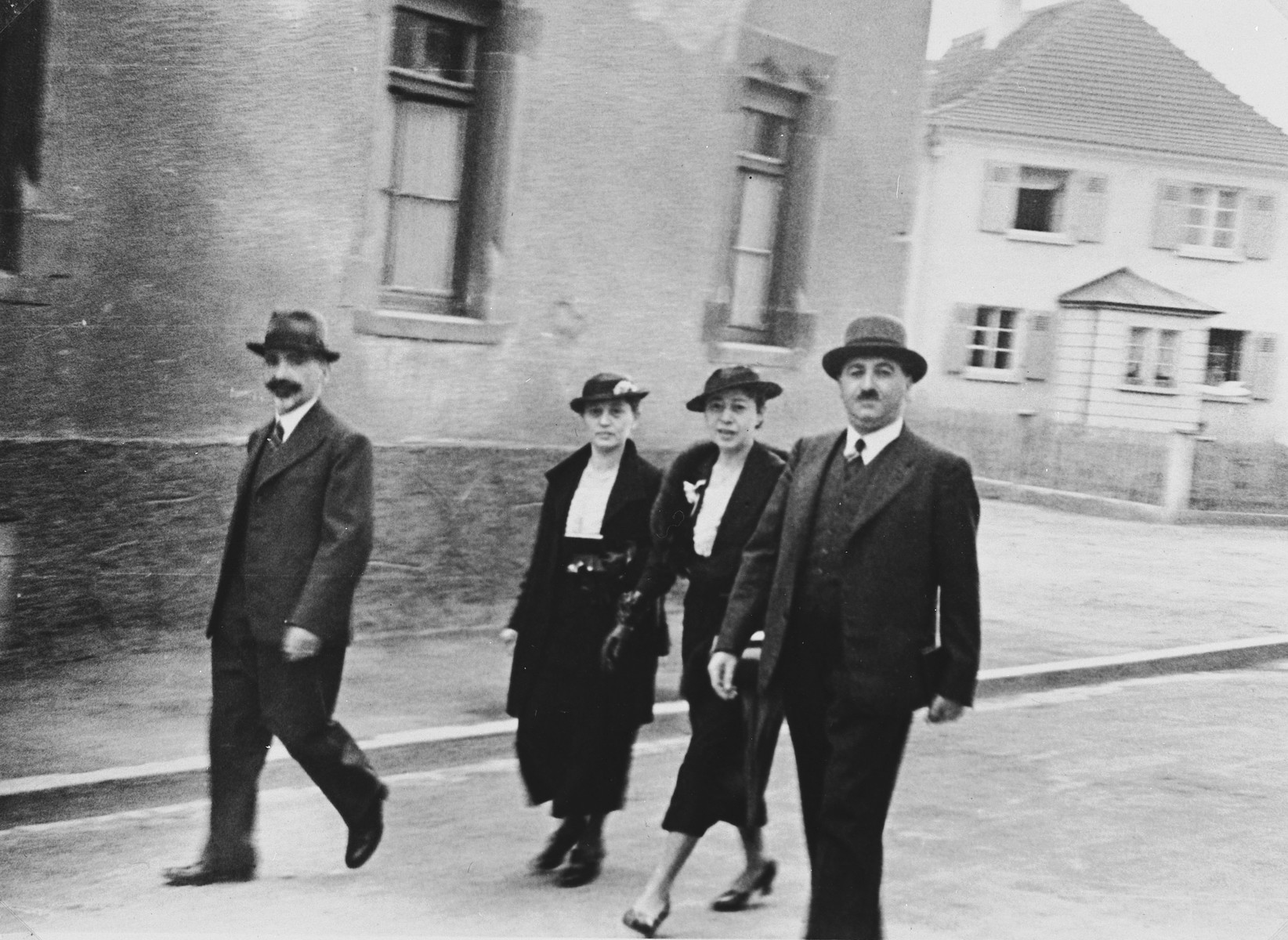 Two Jewish couples walk down Muggensturmstrasse in Breisach, Germany on their way to the synagogue.  Pictured are Hermann, Fanny, Talie and Julius Bähr.  This is part of series of photographs taken of the Breisach Jewish community 1937.  In October 1940 the entire community was deported to the Gurs internment camp in southern France.