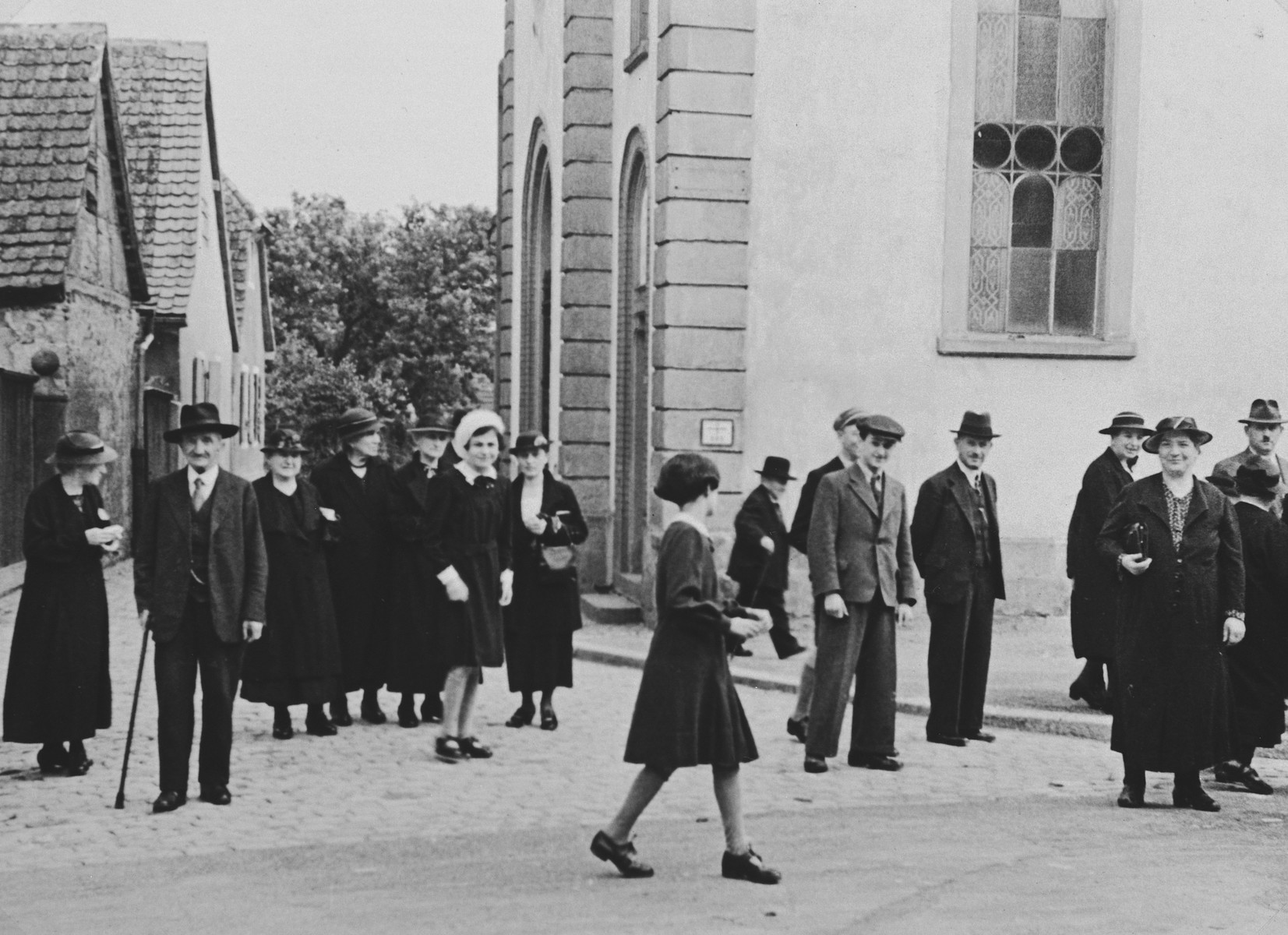 German Jews congregate on the street outside the synagogue in Breisach following Saturday morning services.  Fanny Bähr is in the center of the photograph (with a white feather in her hat, to the right of the woman with the white hat).   This is part of series of photographs taken of the Breisach Jewish community 1937.  In October 1940 the entire community was deported to the Gurs internment camp in southern France.