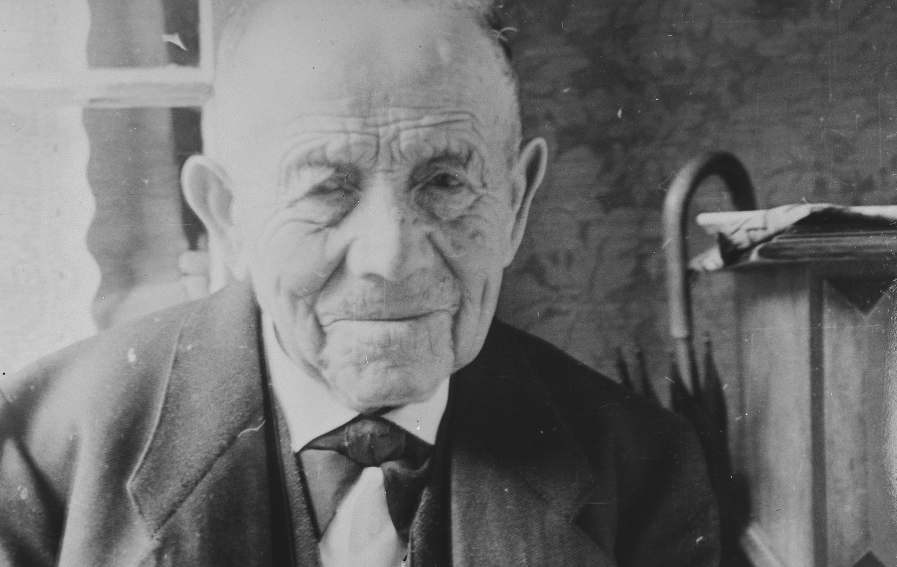 Close-up portrait of a Jewish man in Breisach, Germany.  Pictured is Leopold Geismar.  He was a cousin of the Bährs.  He died in the Jewish Home for the Elderly in Gailingen in July 1939.  This is part of series of photographs taken of the Breisach Jewish community on their way to and from synagogue in 1937.  In October 1940 the entire community was deported to the Gurs internment camp in southern France.