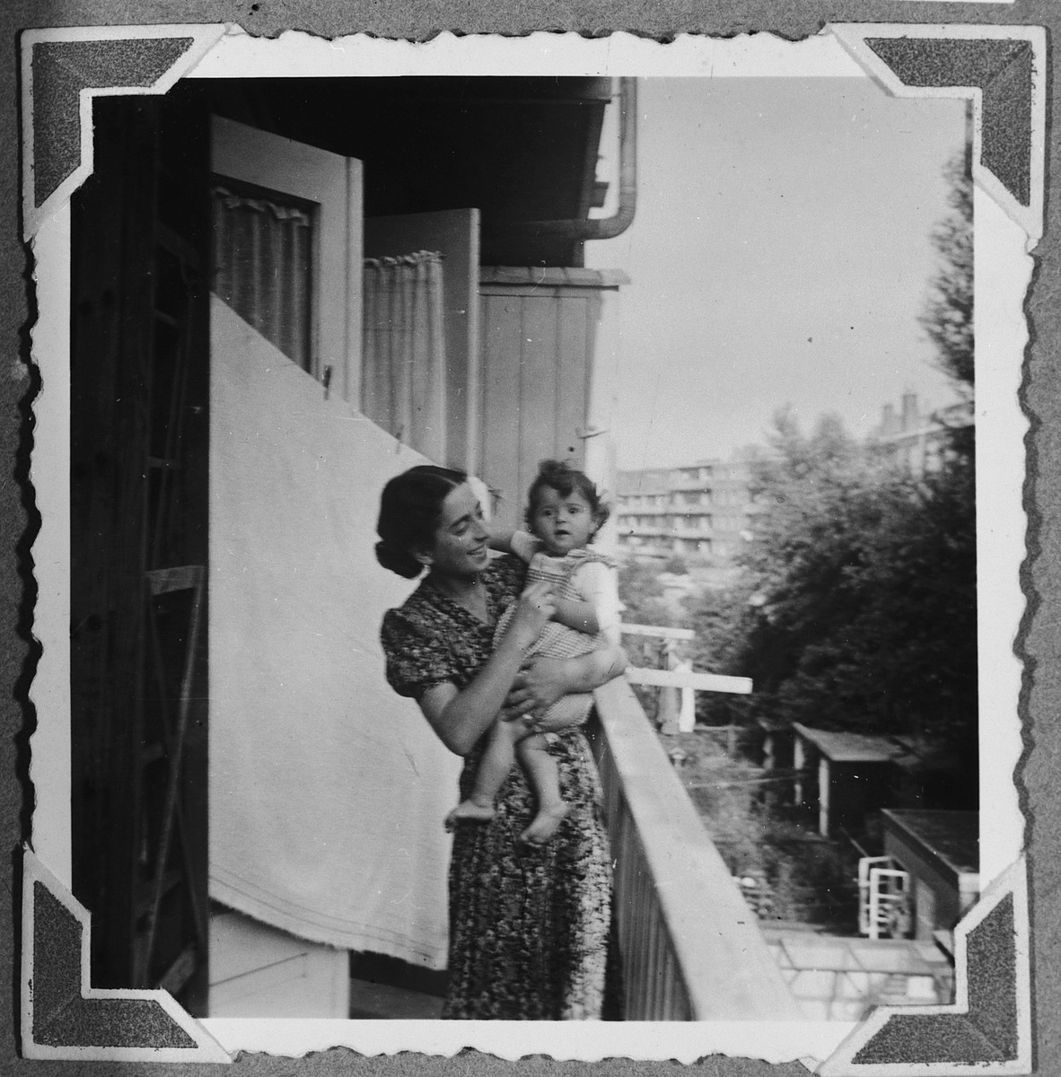 A German-Jewish refugee holds her baby girl in her arms on the balcony to her apartment in Amsterdam where her husband and her family had built a new business.  Pictured are Margot and Suzanne Hochherr.