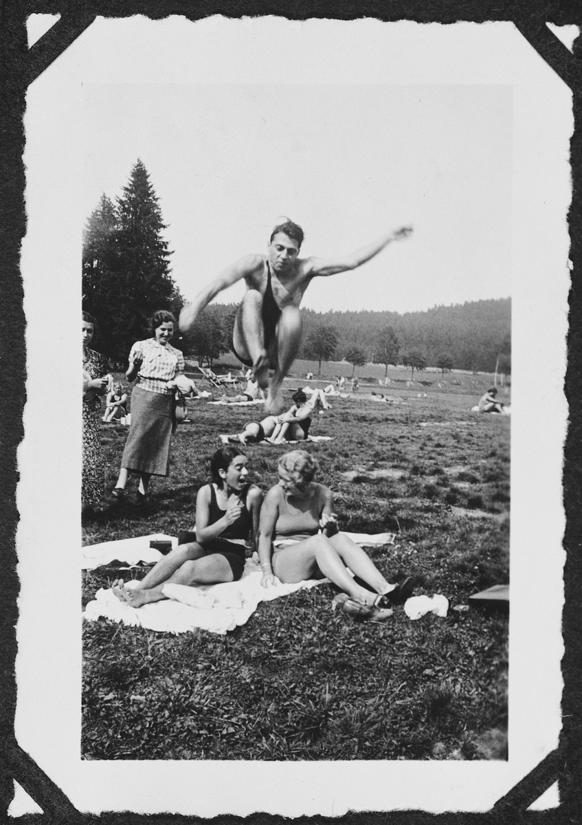 Heinz Bähr leaps over his cousin and a friend during an outing to a park in or near Freiburg.  Seated on the towel is Margot Bähr (left).  Her sister  Ruth is watching on the far left.