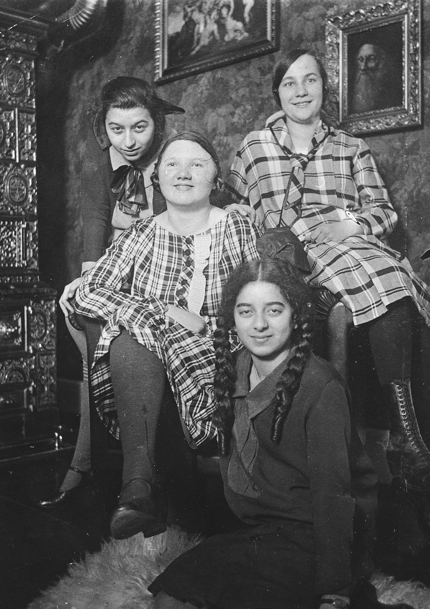 Four German-Jewish teenagers pose together on a Saturday afternoon inside a living room.    Among those pictured are Ruth (left) and Margot (front) Bähr.