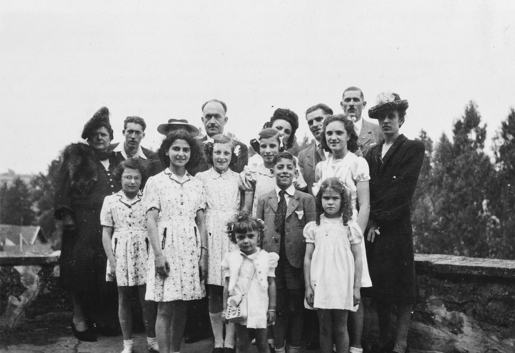 Portrait of two Jewish sisters together with the French family who hid them.  Pictured are Dina and Regine Gartenlaub (front left), Annette Cherrier (left with a hat) and Elly Cherrier (back row, second from right).