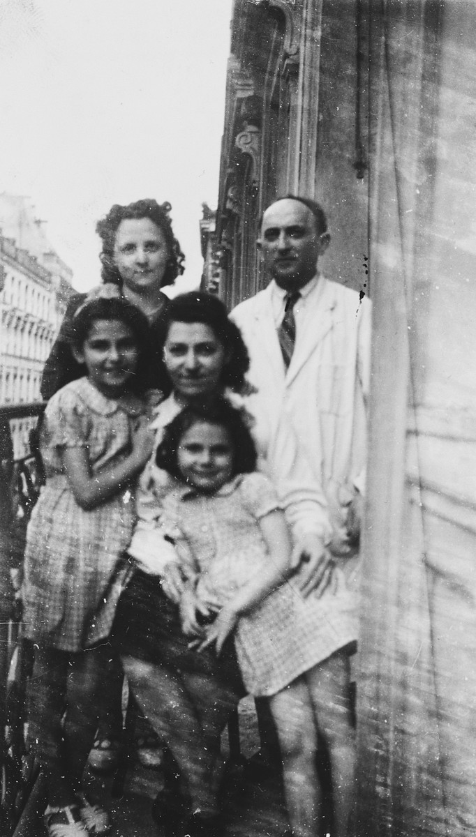 The Gartenlaubs, a Jewish family in Paris, poses together on their balcony shortly before their youngest two daughters went into hiding.  Pictured left to right, front row: Regine, Pauline and Dina Gartenlaub.  Second row: Odette and Jacques Gartenlaub.  Not pictured is the son, Georges.