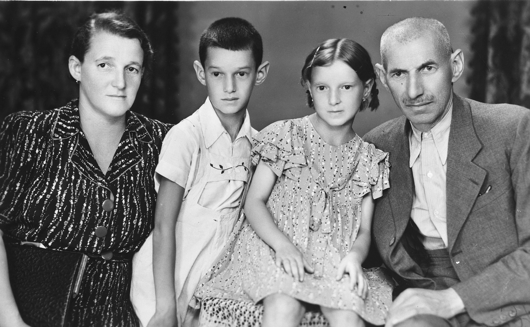 Studio portrait of a Serbian-Jewish family, all of whom later perished in Auschwitz.  Pictured are the brother of Iren Fisch and his family.  From left to right are Ilonka, Hugo, Terike, and Marton Janos Manheim.