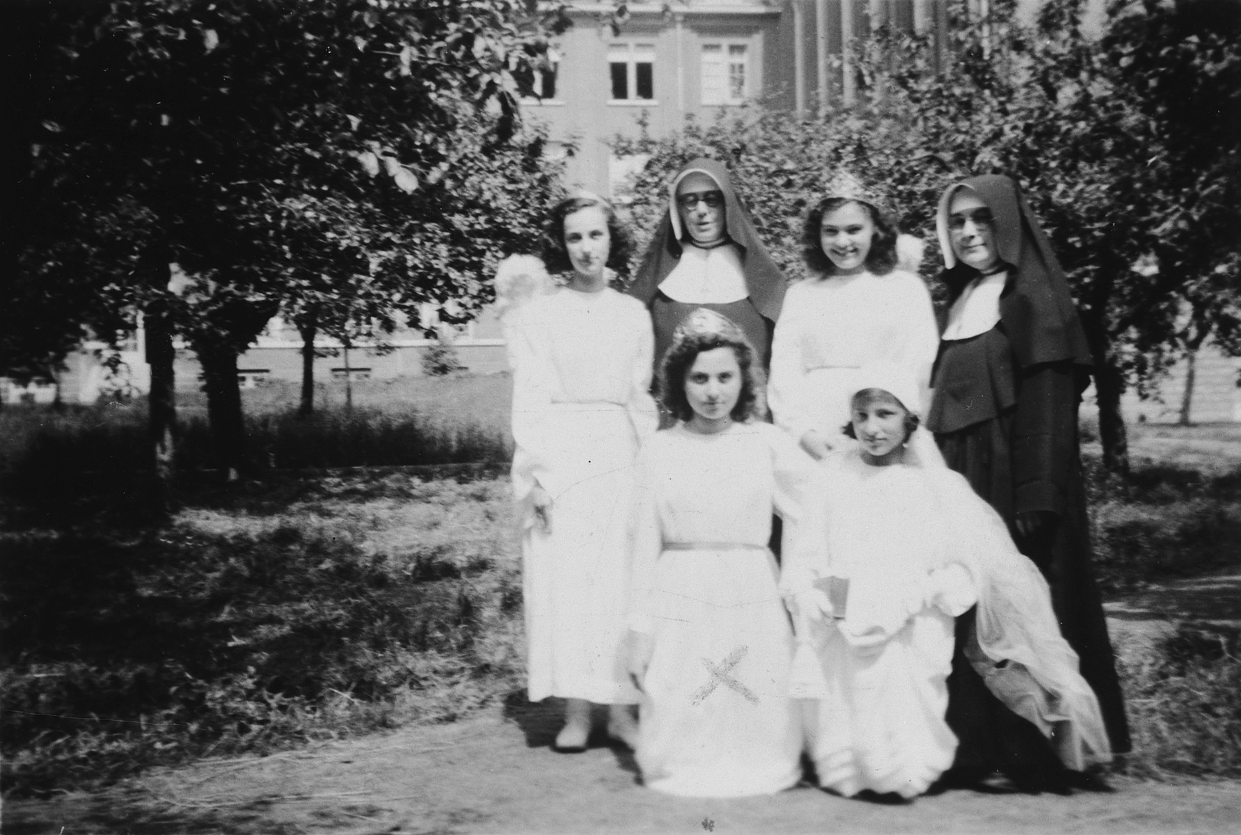 Four girls wearing white dresses pose together with two nuns in the Convent of St. Antoine de Padua on the occasion of the their first communion.  Pictured front row, left is AnneMarie Feller.