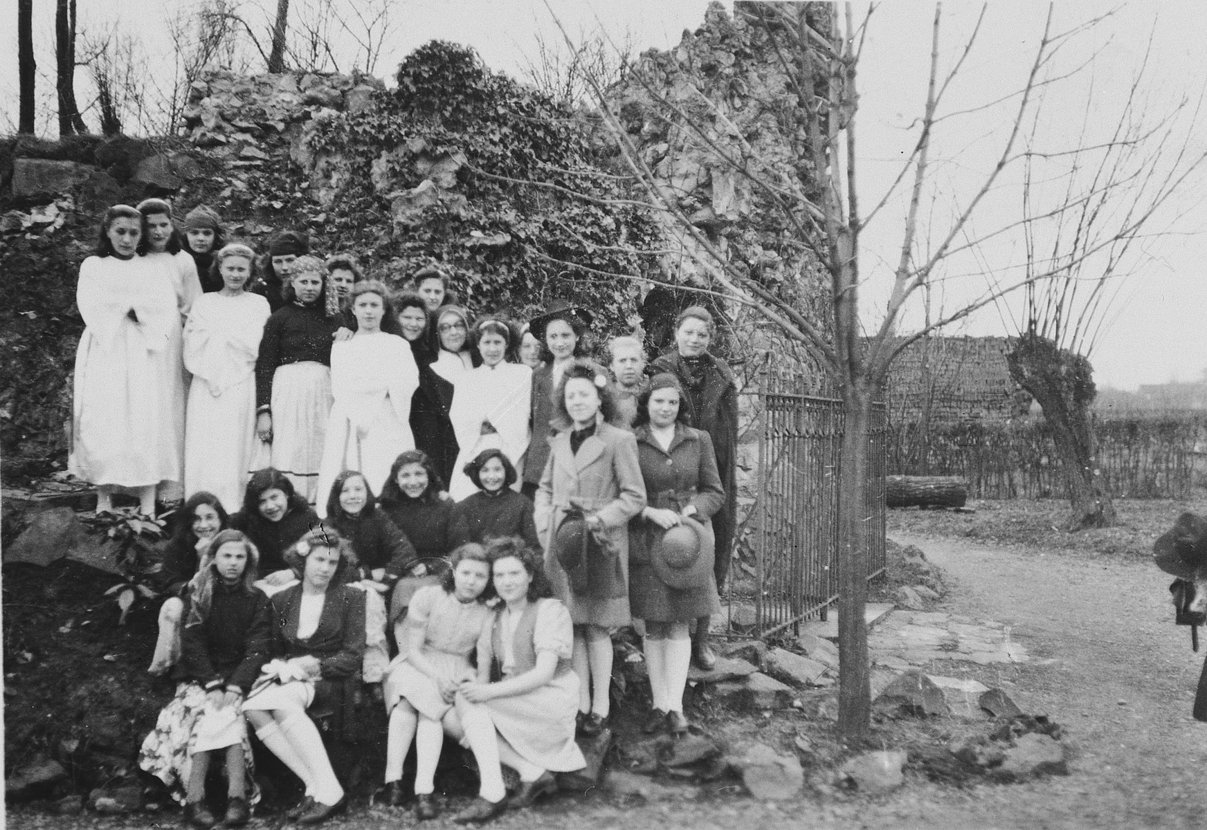 A large group of girls, some wearing white dresses, pose outside a grotto near the Convent St. Antoine de Padua following the first communion of some of the girls.  Among those pictured are Jewish girls hiding in the convent.