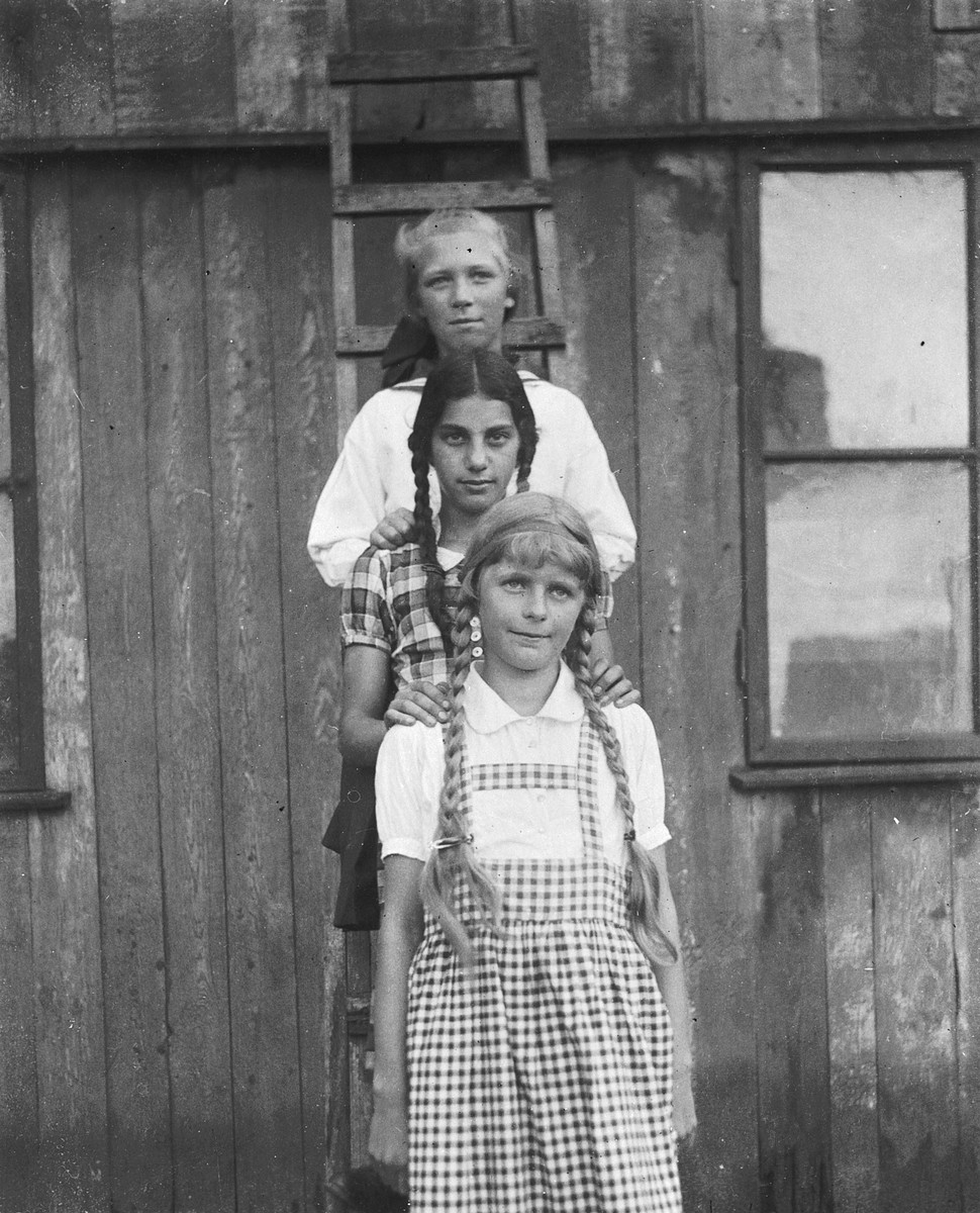 "Three girls stand behind one another on a ladder.  Hildegard Wolff is standing in the middle. The caption says ""Brav und sittsam / die drei auf der Leiter! 1926"" [Honest and decent / the three on the ladder 1926]."