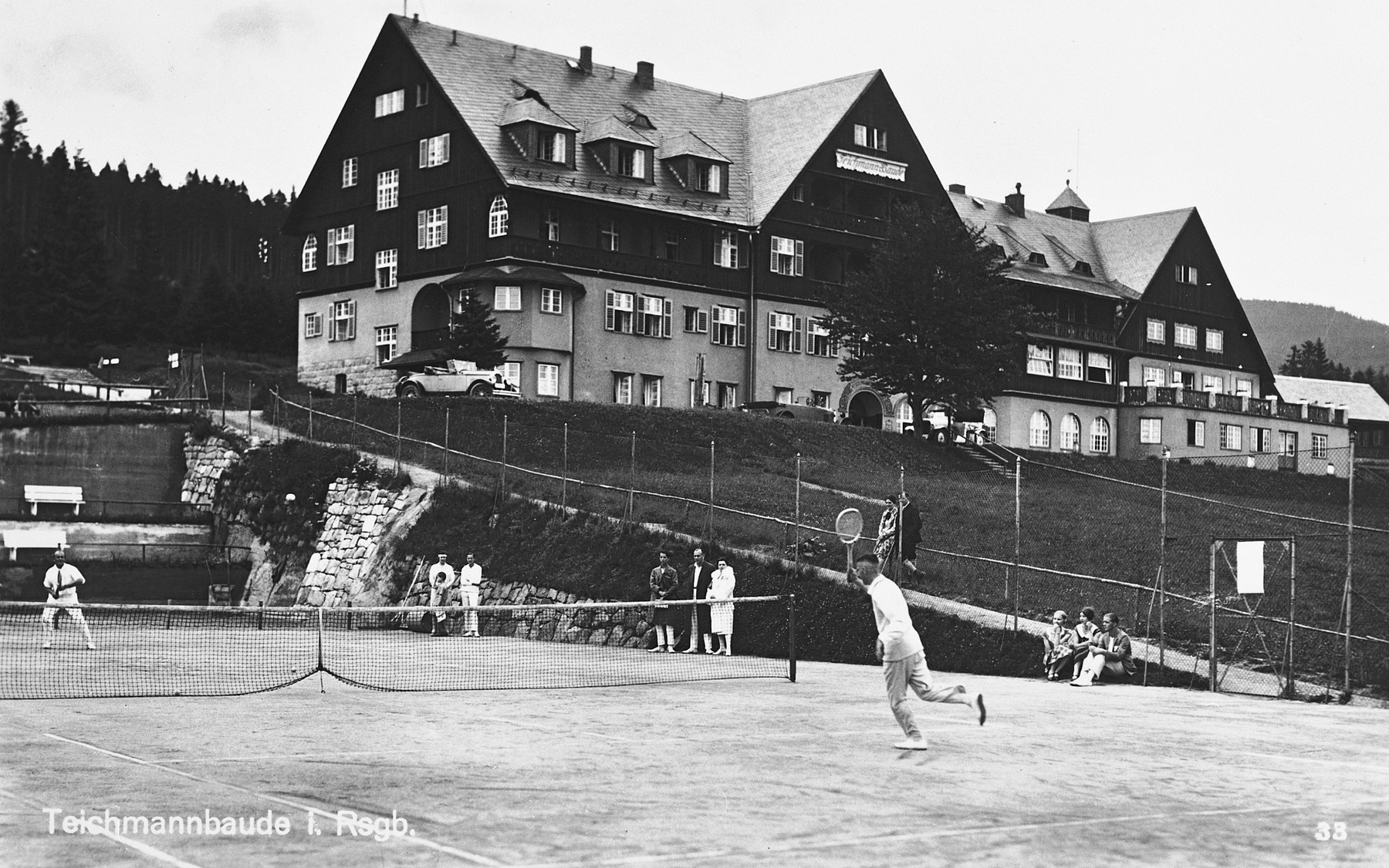 "Visitors play tennis in a resort in Teichmannbaude.  Hildegard Wolff is sitting in the background on the left side between two other people. The caption reads ""Summer holidays 1928."""