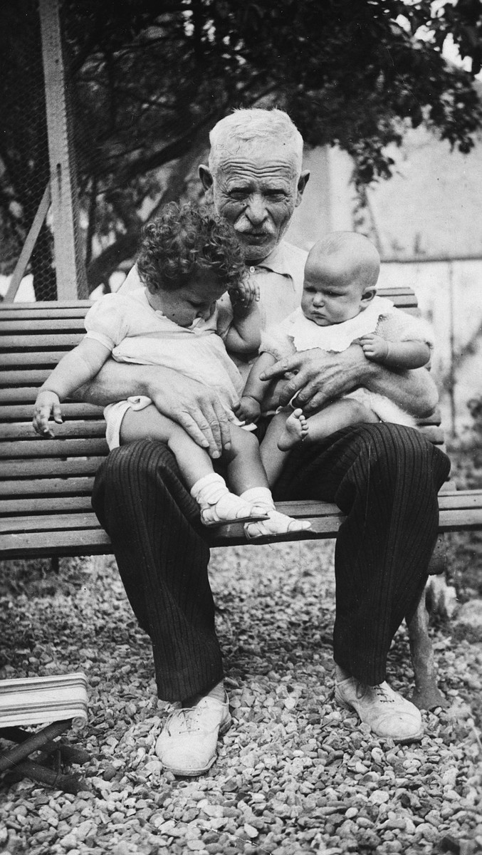 Portrait of a grandfather holding two baby grandchildren on a park bench.  Pictured is Chaim Scharapan with his grandchildren, Nelly and Didi.