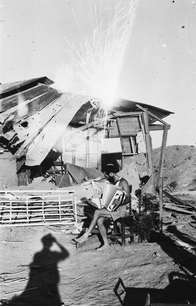A kibbutz member sits next to a rustic shack on a sand dune playing the accordian.