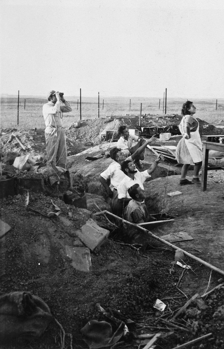 Kibbutz members from Kibbutz Saad emerge from bunkers to stare up at something in the sky.  Pictured in the center is Israel Dubner.