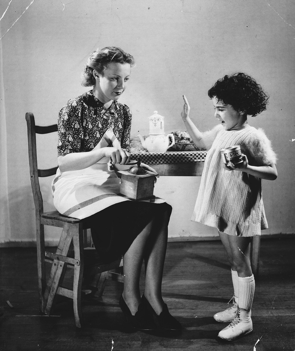 Advertising photograph of a woman holding a coffee grinder and a child holding a can of Nescafe.  The child is Regine Gartenlaub.