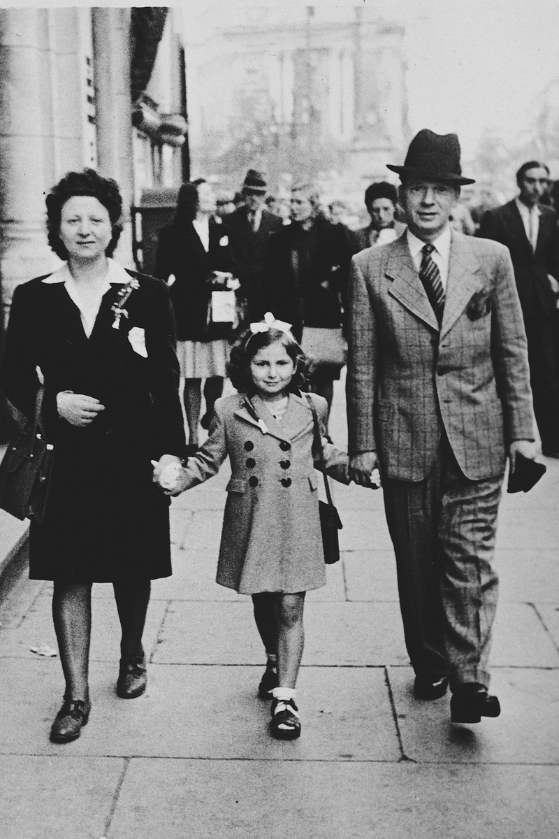 A Belgian-Jewish family walks down a street in Brussels holding hands after being reunited after the war.   Pictured are Fajga, Josiane and Jacques Aizenberg.