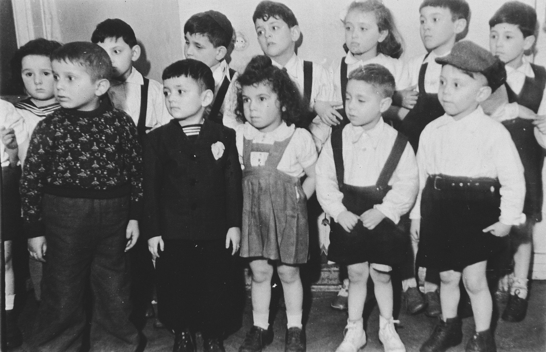 Group portrait of children in the Jewish kindergarten in Lodz standing in two rows for what is probably a children's performance.