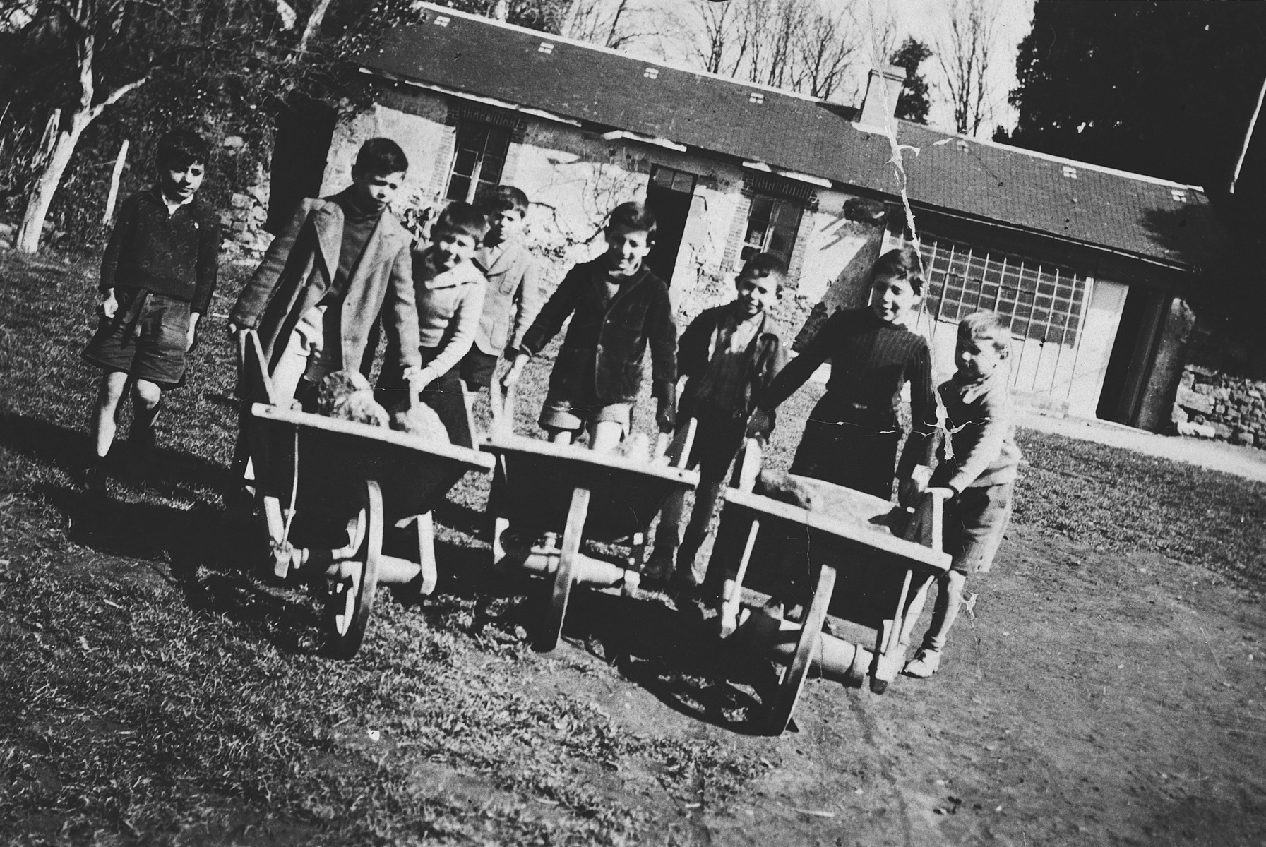 A group of children pushes wheelbarrows on the grounds of the Masgelier children's home in France.  Among those pictured is Israel Lichtenstein.