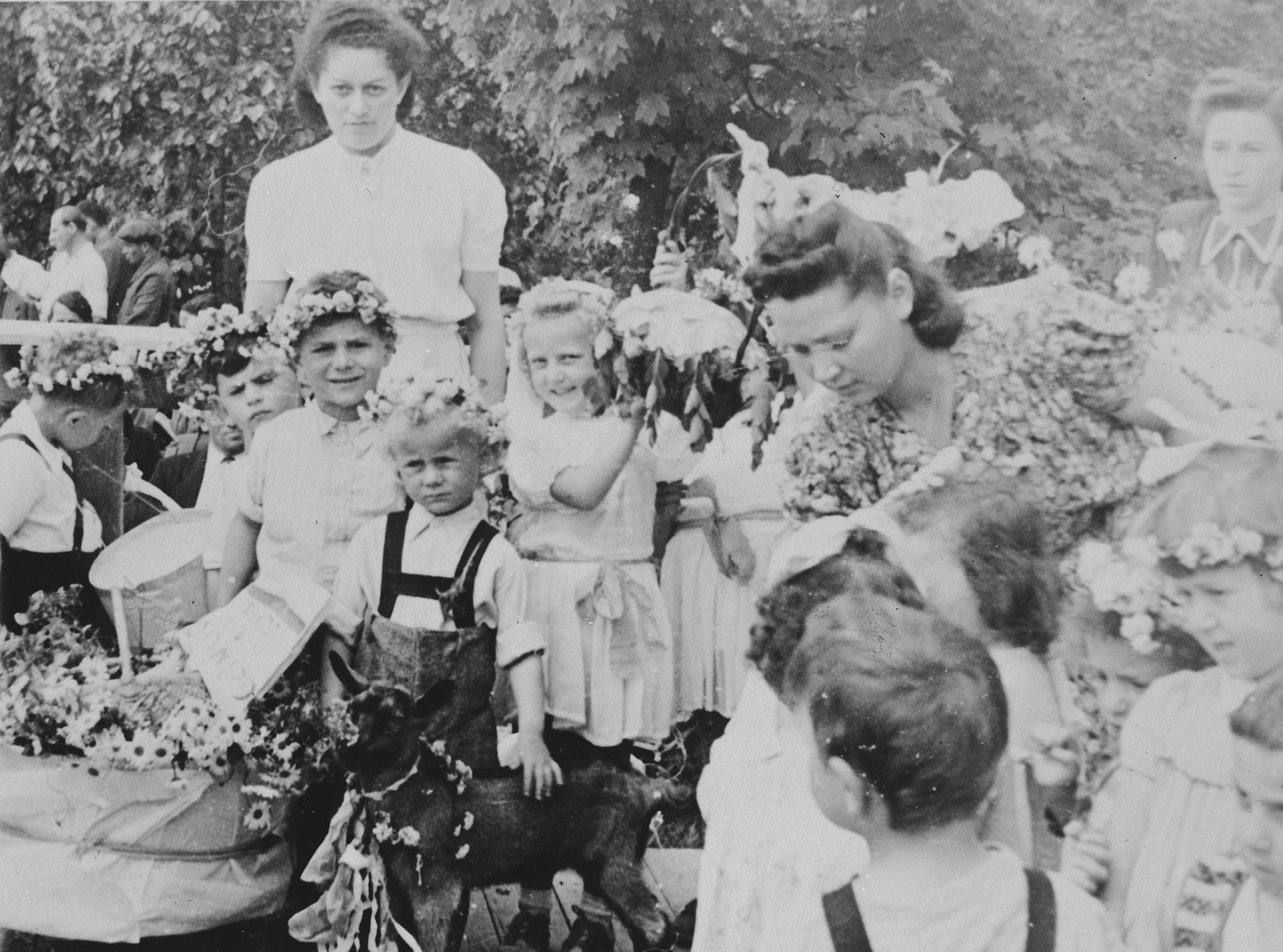 Children wearing wreaths of flowers celebrate Shavuot in a Jewish kindergarten in Lodz.  Among those pictured is their teacher, Rachel Grynglas (leaning over slightly in the center, left).