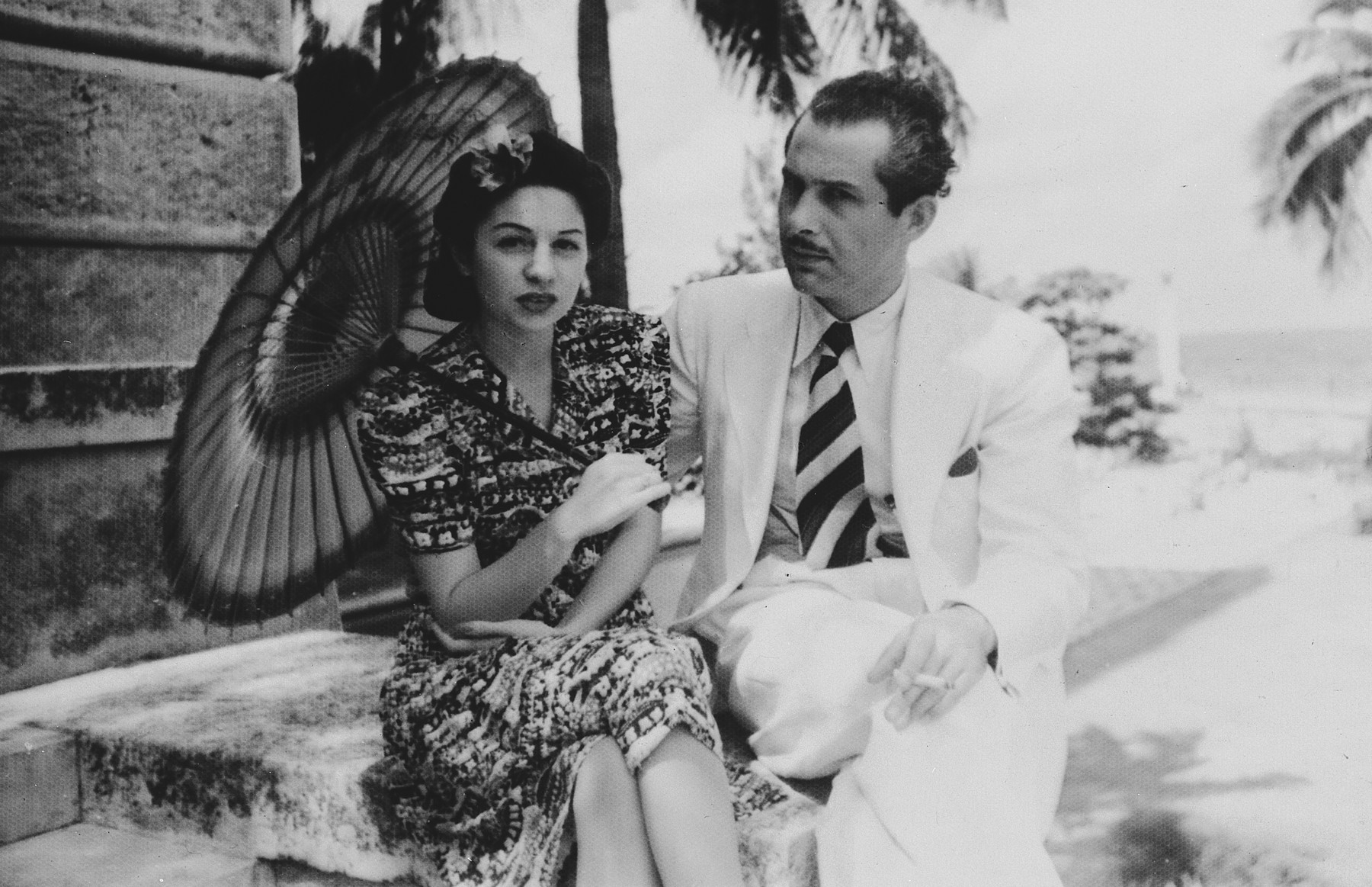 Portrait of a German-Jewish refugee and his wife, holding a sun umbrella and seated outside a building in Cuba.  Pictured is Henry Fink, uncle of the donor.
