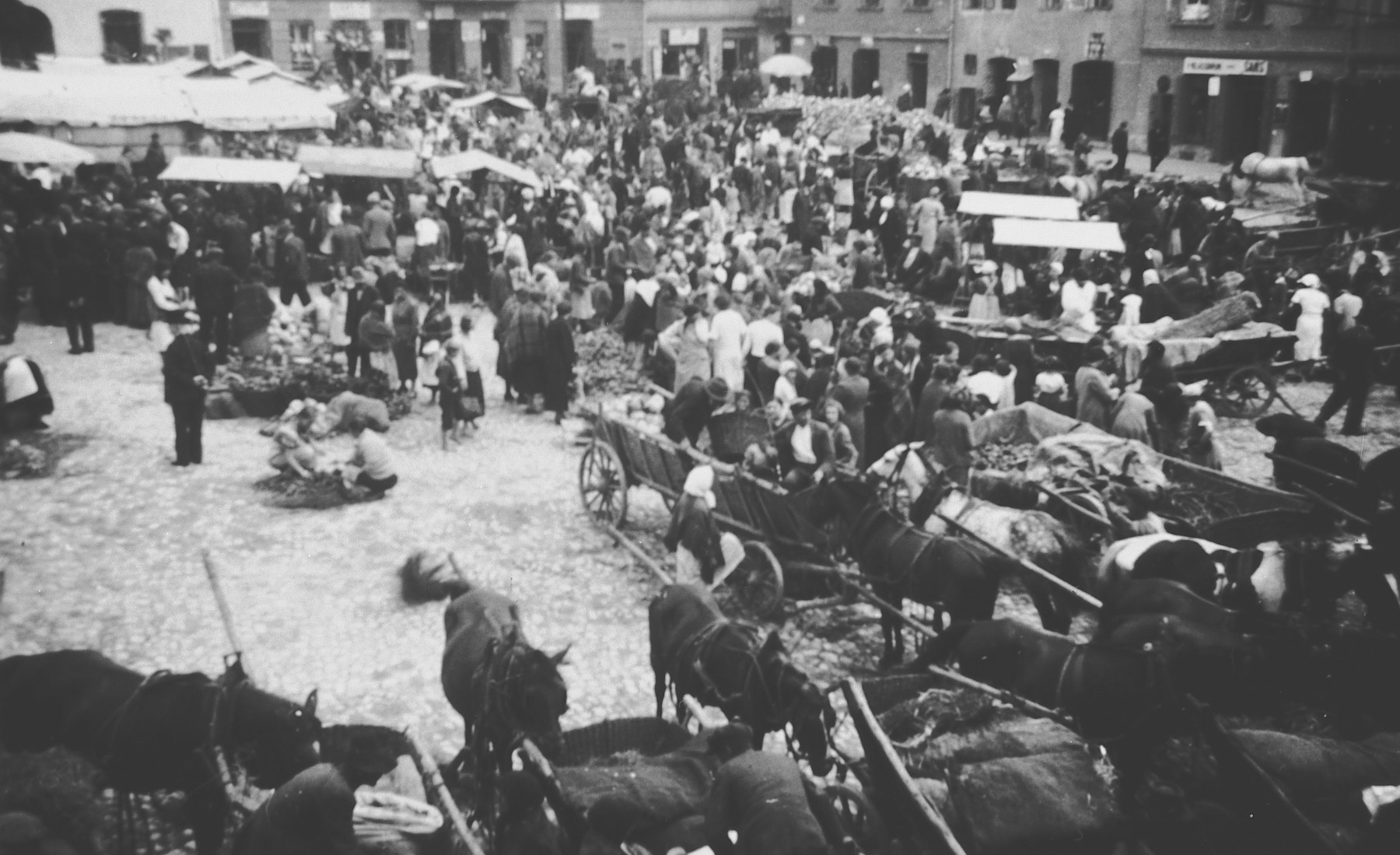 Horse-drawn carts line up on the outskirts of a crowded outdoor market in Oswiecim, Poland [later Auschwitz] before the war.