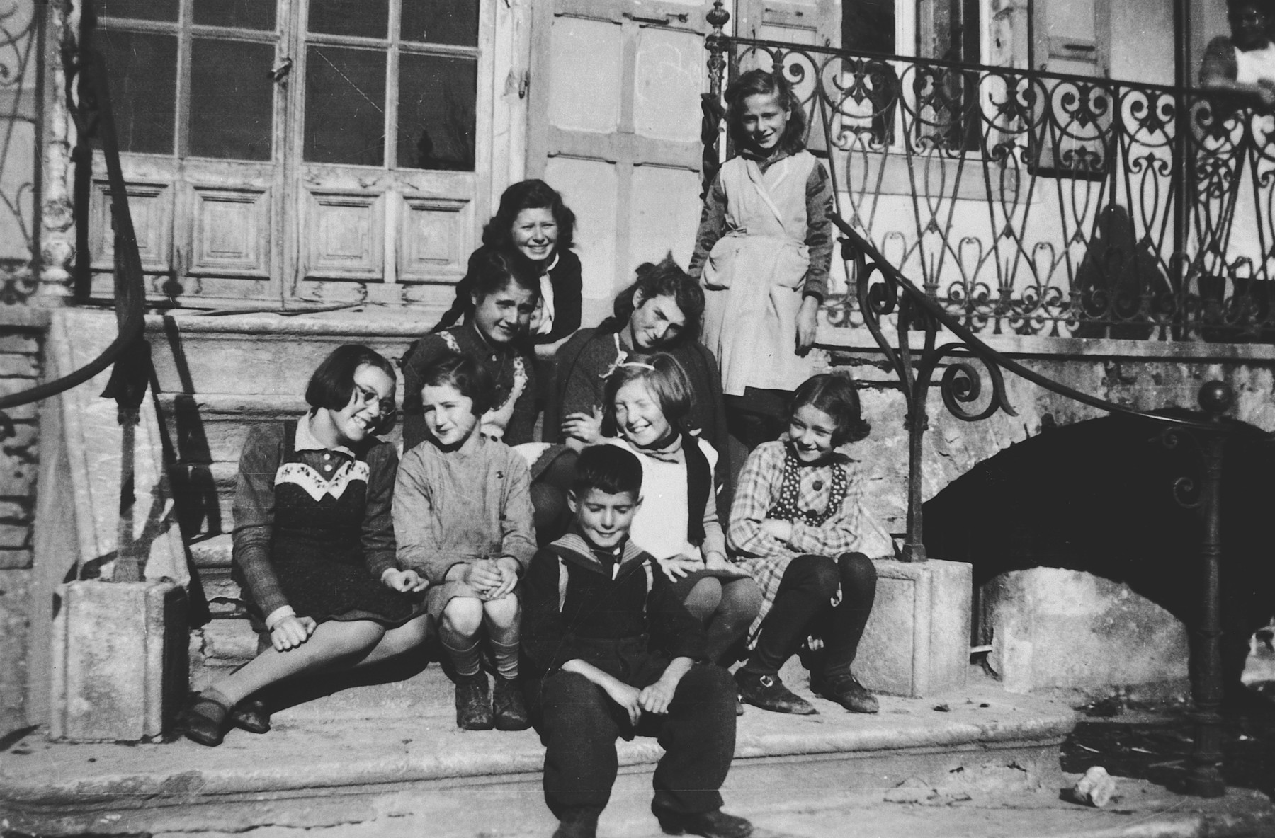 A group of children poses outside on the steps of Pringy, a children's home sponsored by the Swiss Red Cross.  Hilda Krieser is seated in the back.  Her younger sister Anny is seated in the center, wearing a white shirt.  Hannelore Schwarschild (who was taken out of Rivesaltes together with the Krieser sisters) is seated in the far left corner, and Laure Wildmann (later Kolb) is pictured with long braids.  The girl on the top step is Lore Flegenheimer.