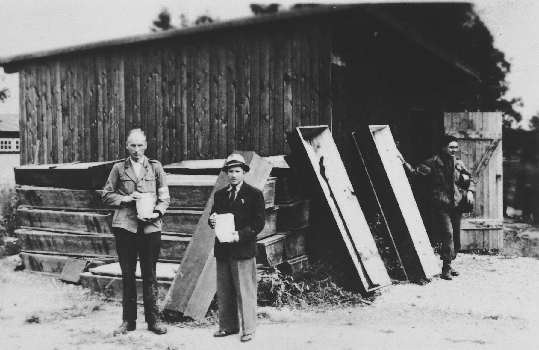 Two men stand in front of a stack of coffins in the newly liberated Dachau concentration camp holding urns of ashes.