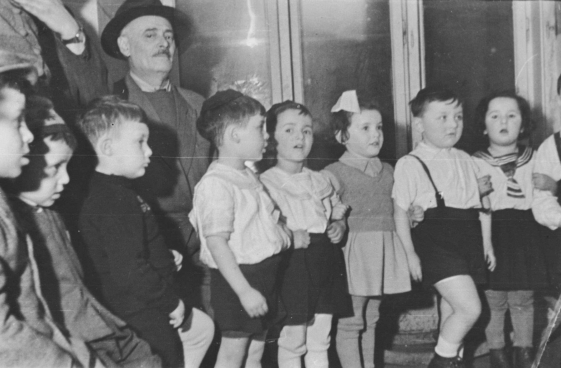 Group portrait of children in the Jewish kindergarten in Lodz standing linking arms during what is probably a children's performance.