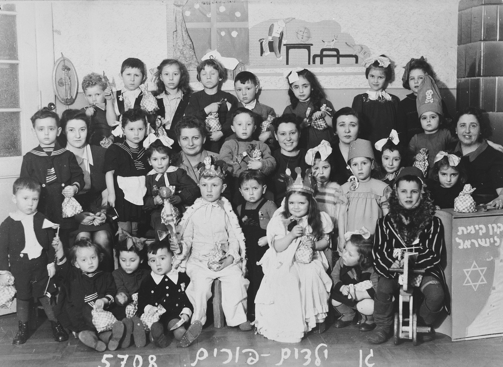 Group portrait of Jewish kindergarten children, some in costume, celebrating Purim in Lodz after the war.  Next to them is a large Keren Kayemet box.  Among those pictured is a teacher, Rachel Grynfeld (seated smiling broadly in the center).
