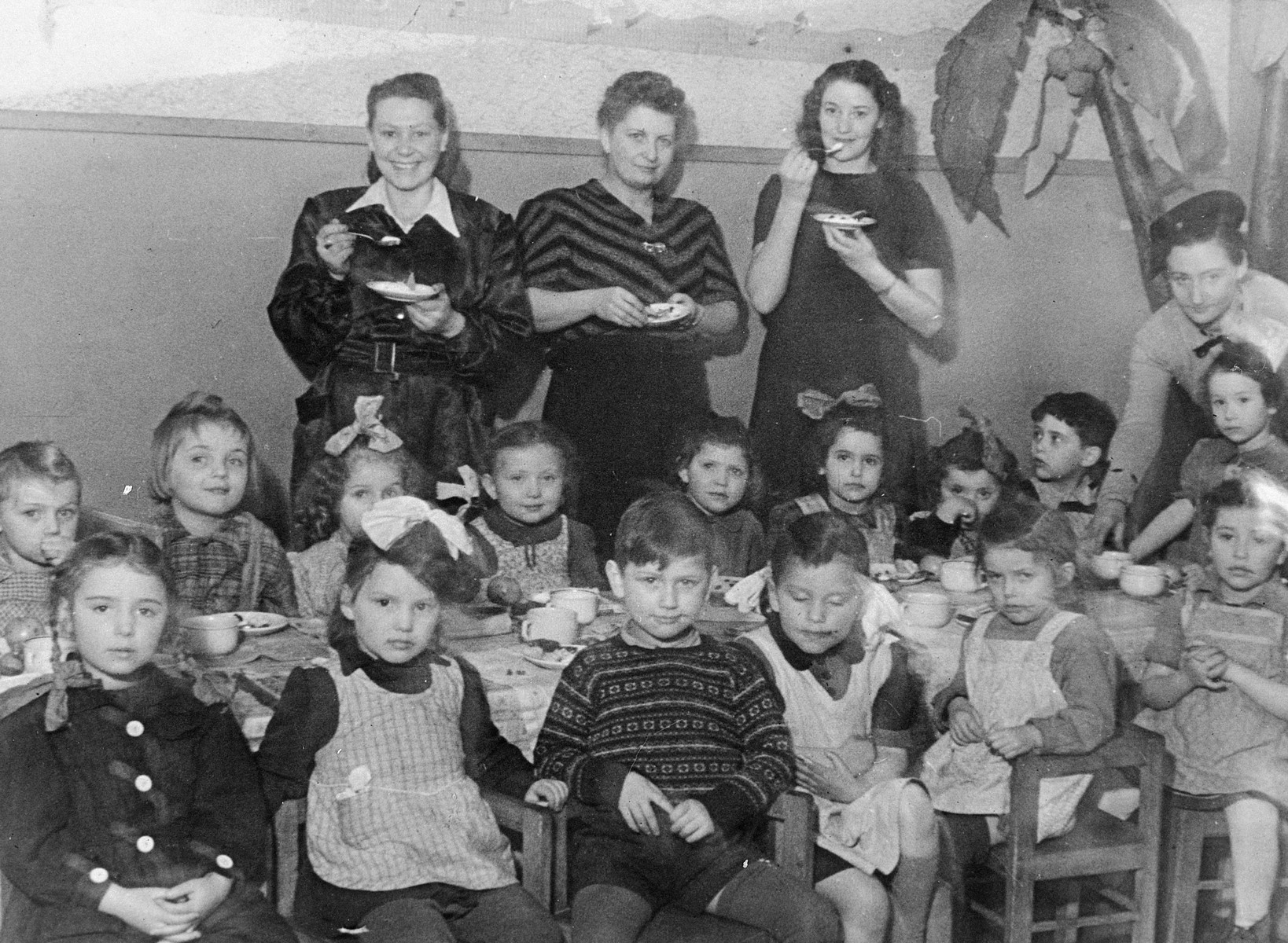 Group portrait of Jewish kindergarten children sitting around a table for a celebration in Lodz after the war.  Among those pictured is a teacher, Rachel Grynfeld (standing on the left).