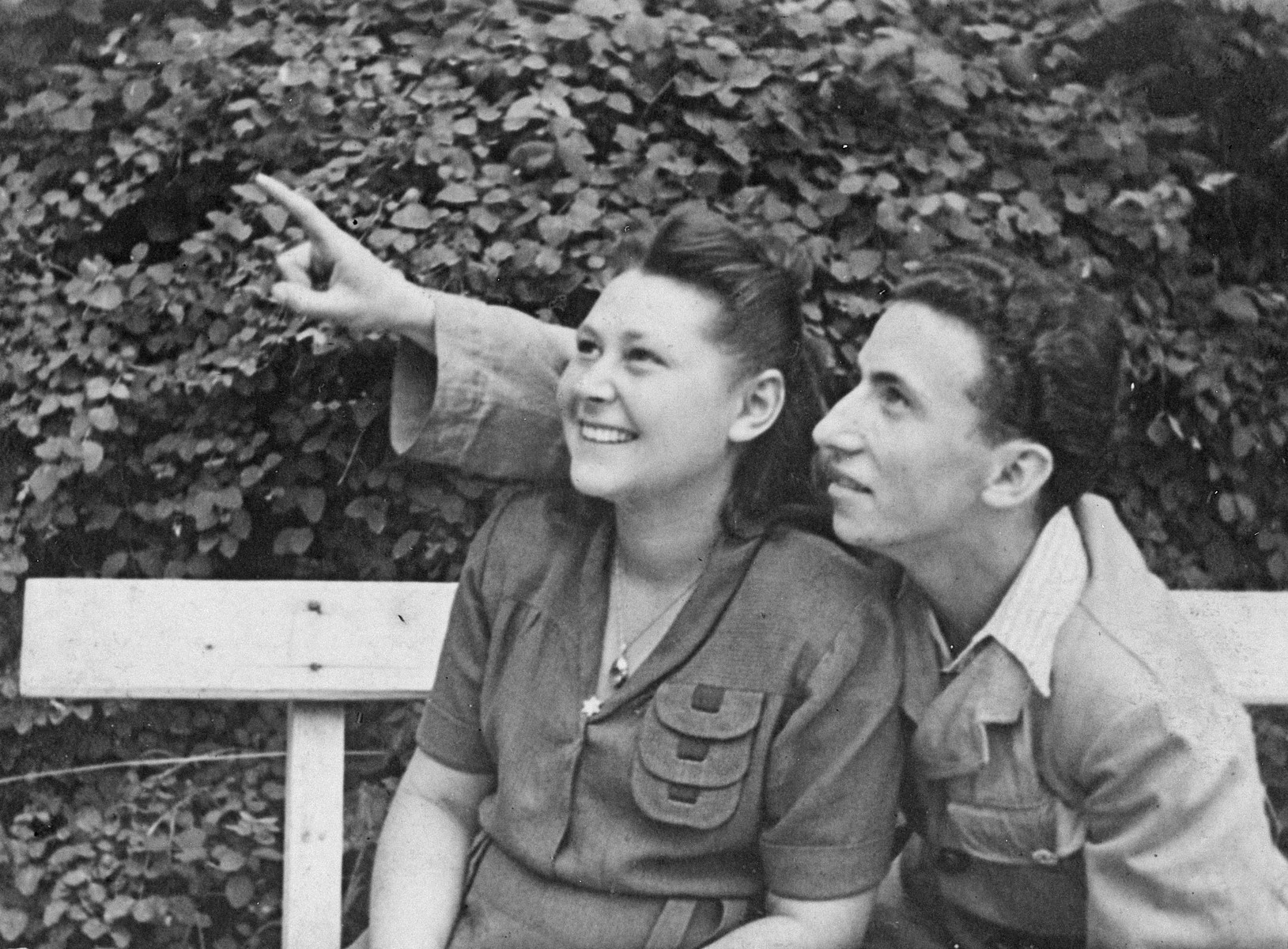 A young couple sits on a bench in the Leipheim DP camp and looks up at something in the sky.  Pictured are Rachel and Lolek Grynfeld.