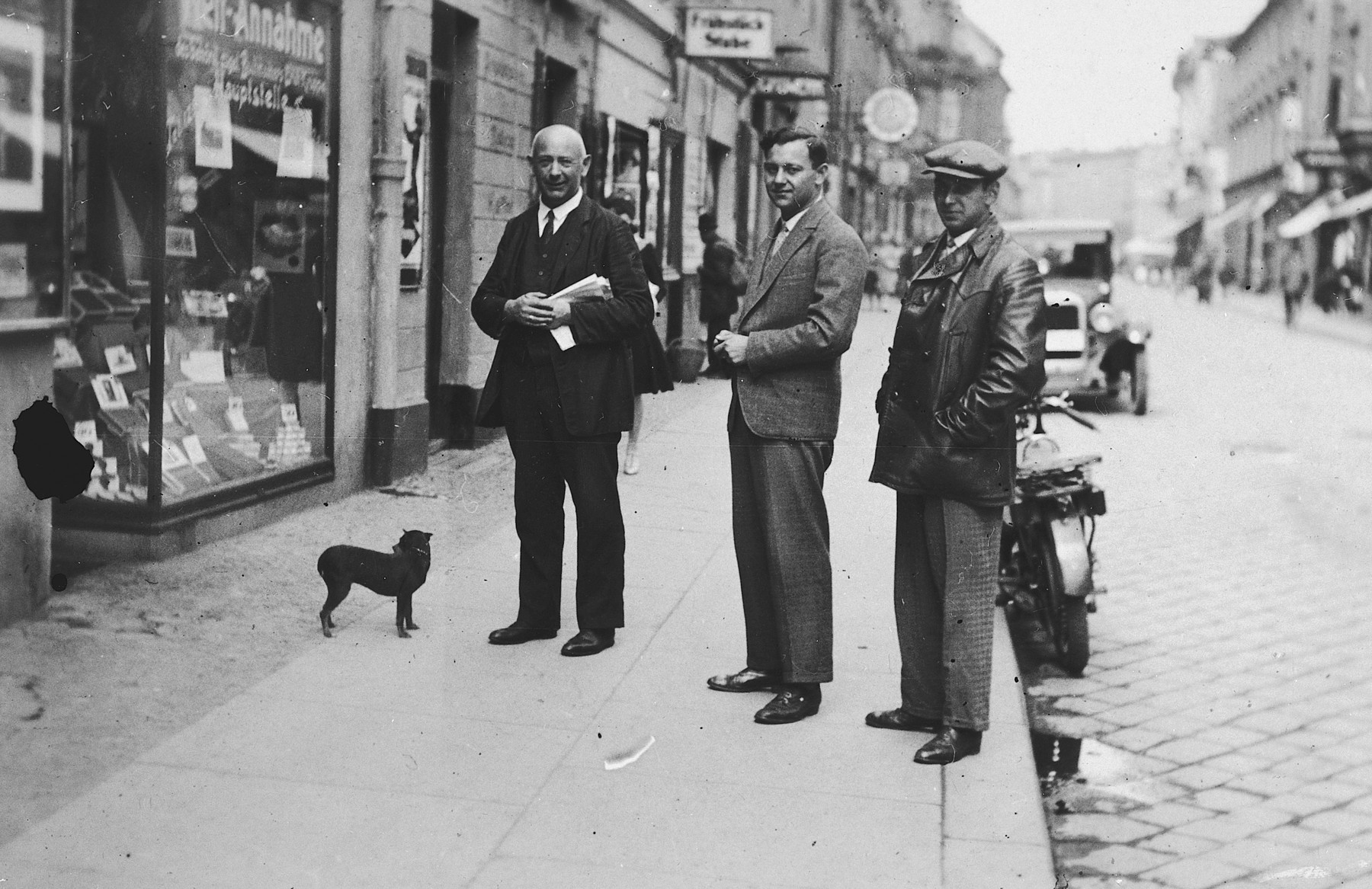 Three German-Jewish men stand next to a small dog on the sidewalk of a commercial street in Breslau.  Pictured are Manfred Fink, his father and brother.