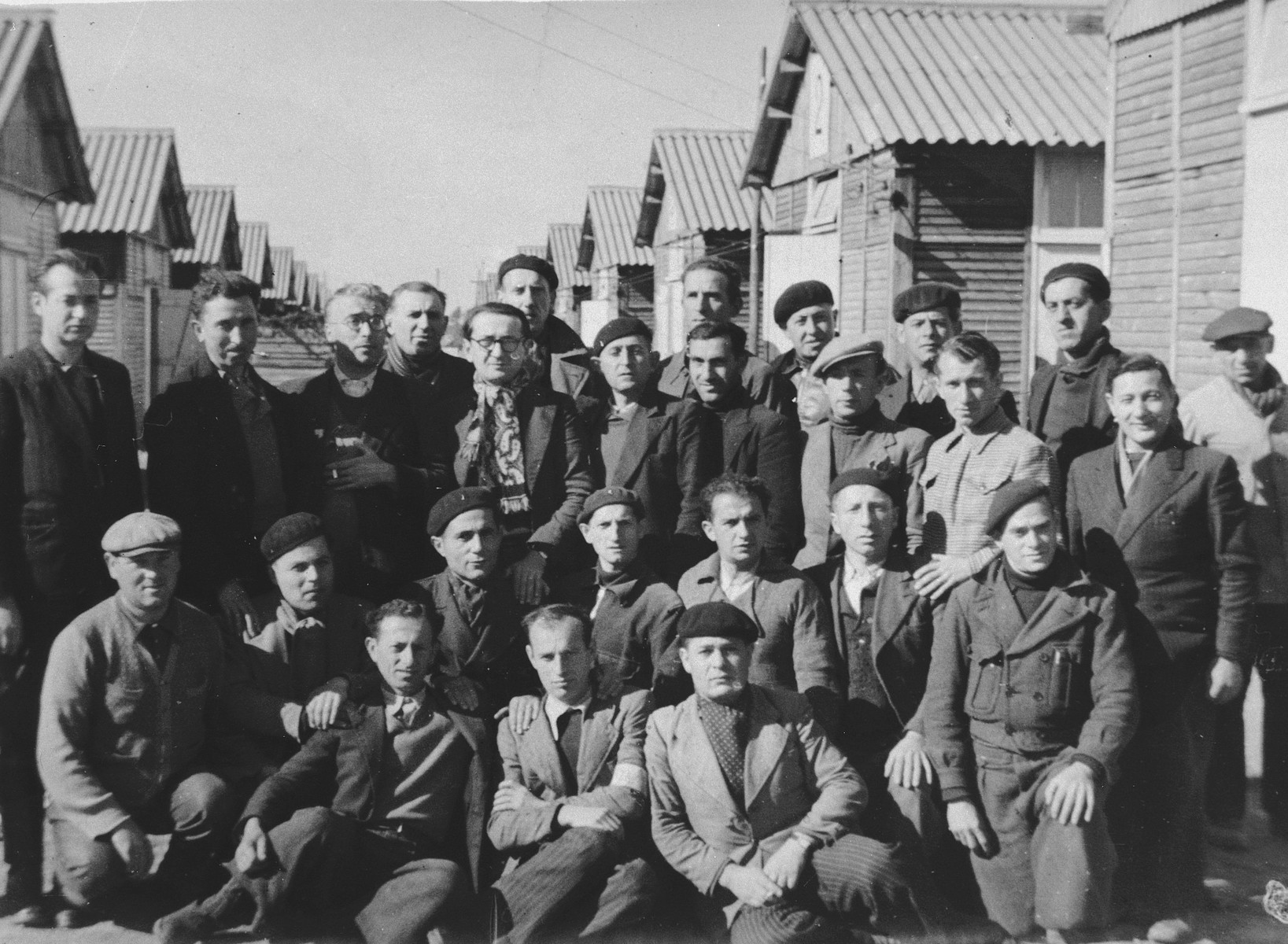 Group portrait of male prisoners in front of the barracks of the Beaune-la-Rolande internment camp.  Among those pictured is Menachem Mendel Lichtenstein (middle row, fifth from the left).