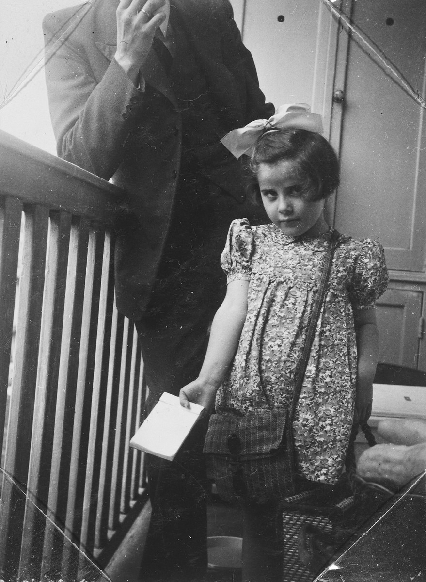 A young Jewish girl with a large bow in her hair stands on the balcony of the home where she was hiding.  Pictured is Rita Serphos.
